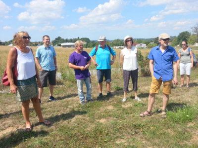 Andrea Schwarz MdL (ganz links) und weitere Interessierte lauschen den Erläuterungen von Dieter Mitsch (lila T-Shirt) auf dem Sulzfelder Streuobst-Erlebnispfad.