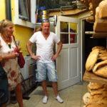 Bäcker Roger Eschbach mot der grünen Gemeinderätin Sonja Günthner (links) und Andrea Schwarz MdL in seiner Backstube vor dem Regal mit unterschiedlichen frisch im Holzofen gebackenen Broten.