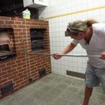 Bäckermeister Roger Eschbach führt vor, wie in seinem neuen Holzofen Brot gebacken wird.