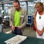 Dr. Heiko Hentrich, Leiter des Teams Arzneipflanzenkulturen in der DHU, erklärt Andrea Schwarz MdL wie die Samen gesäät und die Jungpflanzen in der Terra Medica gezogen werden - vom Gewächshaus, über das Kühlhaus, bis sie dann ins Freie gepflanzt werden können.
