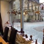 Ein Blick aus dem Wahlkreisbüro von Andrea Schwarz MdL in die weihnachtliche Melanchthonstraße in Bretten. Geziert werden die Schaufenster gerade von Rosenwurzelfiguren von Martin Rausch und kunstvollen Mobiles aus Naturmaterialien einer Künstlerin.